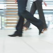 Image of legs walking along a sidewalk.