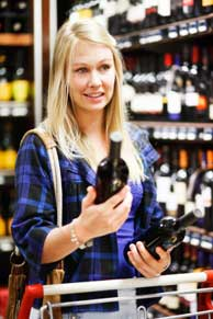 A woman making a decision about brands of wine at a grocery store.