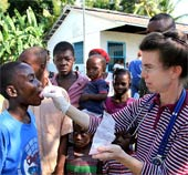 An aid worker gives medicine to Haitian child in Léogâne