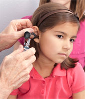 A doctor examining the inside of a young girl's ear while her mother looks on.
