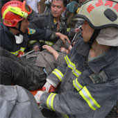 Sichuan earthquake rescue workers carrying an injured person.