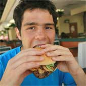 Teenage boy eating a hamburger.