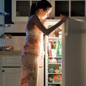 Woman at open refrigerator.