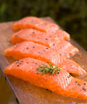 Four fresh salmon fillets on wooden planks ready for grilling.