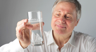 a man drinks a glass of water