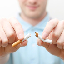 A man breaks a cigarette in half.
