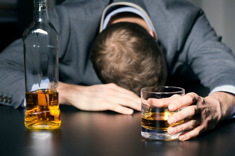 The 7 best hangover cures backed by science man with alcohol in hand and resting head on table the easiest way to ccuart Choice Image