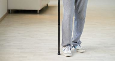 Person with Mutliple Sclerosis walking with a cane