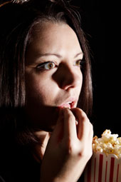 A girl eating popcorn at a movie theater.