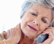 Woman on phone holding neck in pain