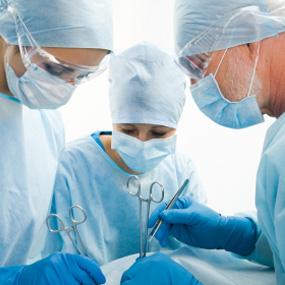 three doctors operating on patient