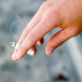 hand holding smoking cigarette