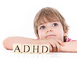 Distracted boy with blocks spelling ADHD