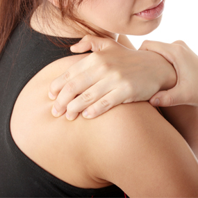 woman griping her shoulder with hand