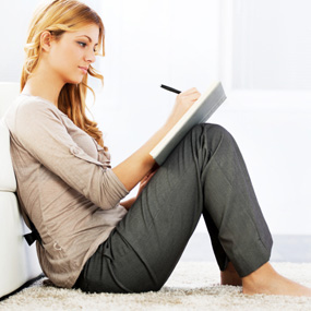 woman sitting writing in notebook about crohn's