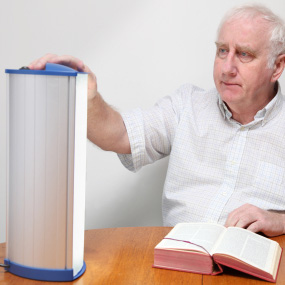 Man with book touching a device