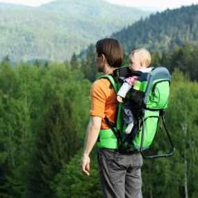 man with baby in back carrier looking at mountains and trees