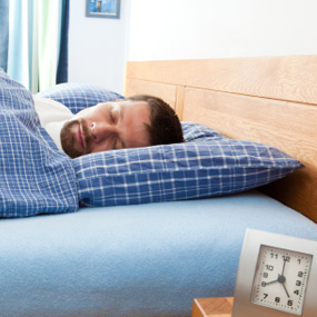 man asleep in bed with clock in foreground