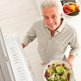 man in kitchen holding salad