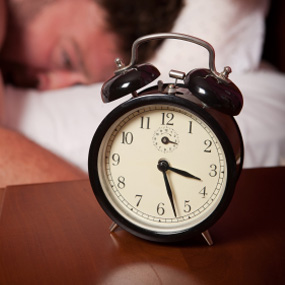 nightstand alarm clock with man asleep in background