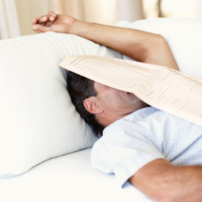 man laying in bed with newspaper covering face