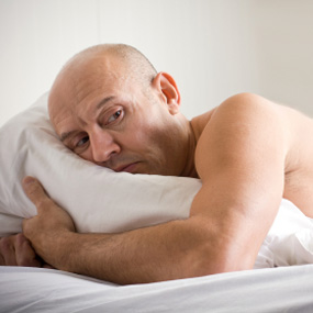 man laying in bed concerned