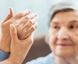 older woman holding up hand