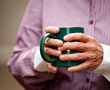 arthritic hands holding coffee mug