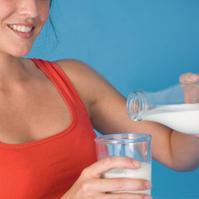 A woman pouring a glass of milk.