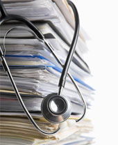 Pile of medical records with stethoscope.