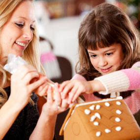 Little girl and mom making a gingerbread house.