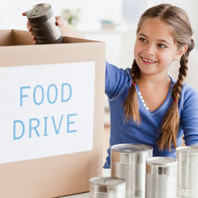 "Girl loading food into a box labeled ""Food Drive."""
