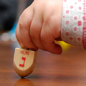 A child playing with a dreidel.