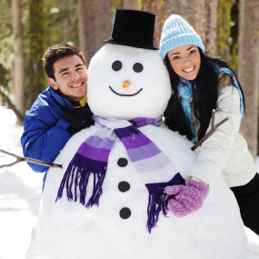 Girl and guy positing with snowman.