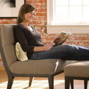 A woman reading a magazine on a chair, using a lumbar cushion to support and massage her lower back.