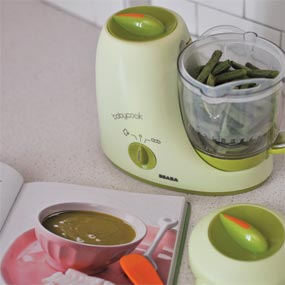 Baby food maker, with fresh green beans in it prepared for steam-cooking.