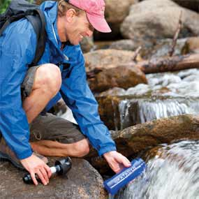 A man filling a water bottle purifier with water from a mountain stream.