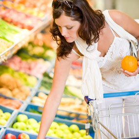 A woman shopping for fruit in a grocery store.