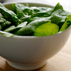 Fresh spinach leaves in a bowl.
