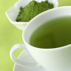A bowl of fresh green tea leaves and a cup of brewed green tea.