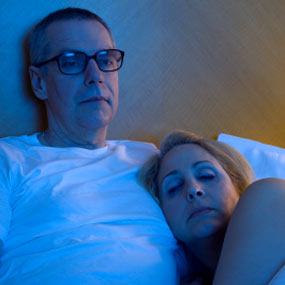 Man and woman watching tv in bed.