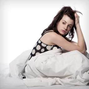 A woman looks tired as she sits up in bed.