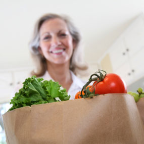 A woman with a grocery bag full of food.