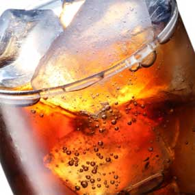 Close up of the carbonation in a glass of soda.