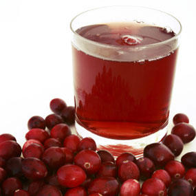 Cranberries next to a glass of cranberry juice.