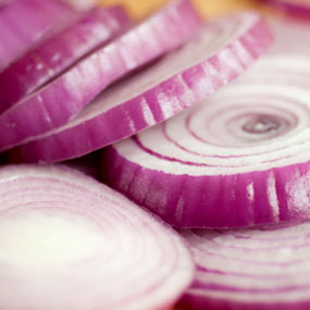 Slices of red onion, raw.