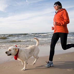 A woman runs with her dog.