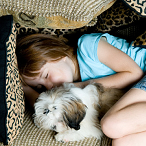 A girl naps with her dog.