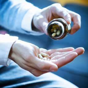 A man pouring pills from a pill jar into his hands.