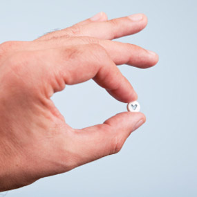 A hand holding a single valium pill.